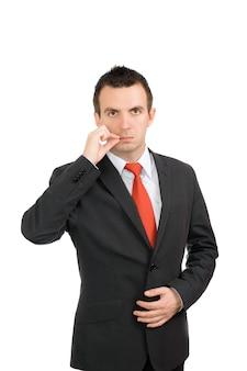 Wesoły młody biznesmen być w świecie przez siebie-pokaż gest zamknij usta. odosobniony