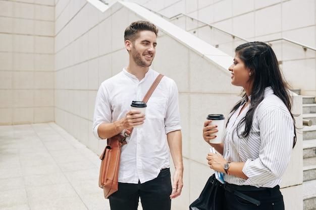 Wesoły młody biznesmen i bizneswoman, picie wyjąć kawę, stojąc na zewnątrz budynku biurowego