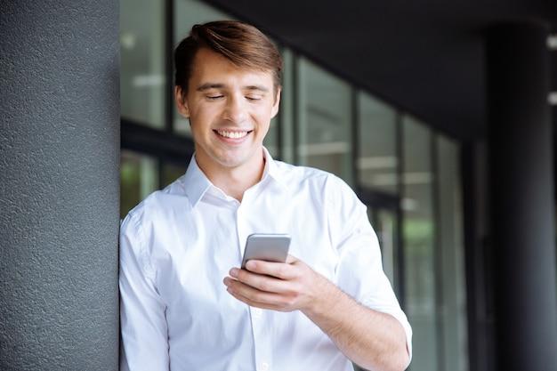 Wesoły młody biznesmen rozmawia przez telefon komórkowy w pobliżu centrum biznesowego