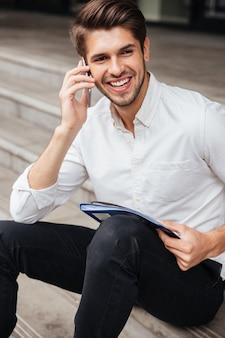 Wesoły młody biznesmen siedzi i rozmawia przez telefon komórkowy na zewnątrz