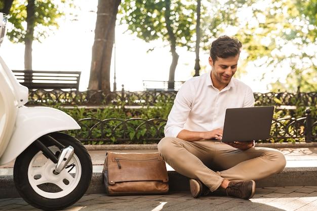 Wesoły młody biznesmen siedzi na zewnątrz, pracując na komputerze przenośnym