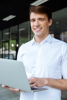 Wesoły młody biznesmen trzymając laptopa i rozmawiając przez telefon komórkowy w pobliżu centrum biznesowego