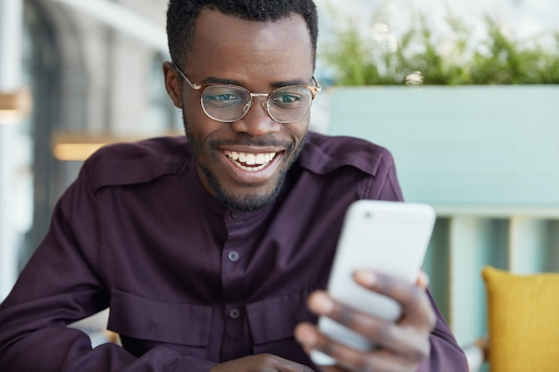 Wesoły młody biznesmen w okrągłych okularach i strojach wizytowych sprawdza aktualności na nowoczesnym smartfonie, podłączonym do bezprzewodowego internetu