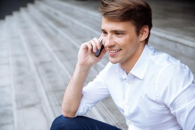 Wesoły młody biznesmen za pomocą smartfona w pobliżu centrum biznesowego