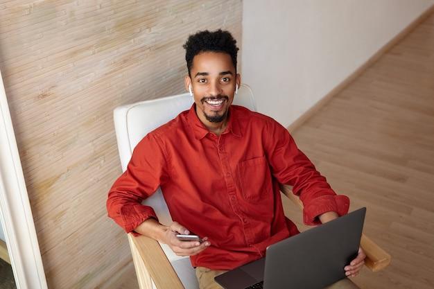Wesoły młody brązowooki brunet, brodaty ciemnoskóry mężczyzna z radością patrzy z uroczym uśmiechem podczas pracy poza biurem z telefonem komórkowym i laptopem