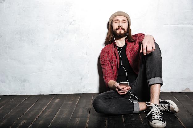 Wesoły młody brodaty hipster mężczyzna w kapeluszu ubrany w koszulę w klatce siedzący na podłodze odizolowanej nad ścianą podczas słuchania muzyki przez słuchawki