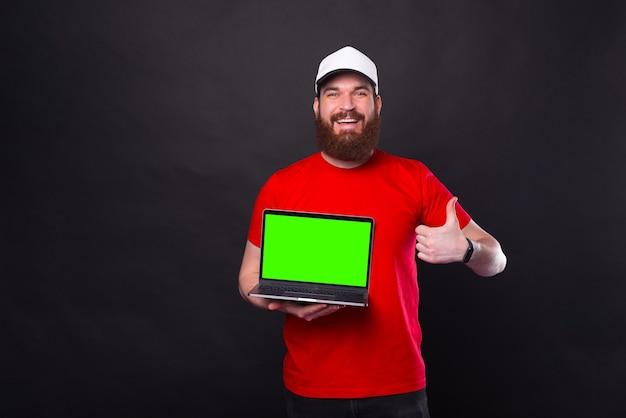 Wesoły młody brodaty mężczyzna pokazuje kciuk i zielony ekran na laptopie