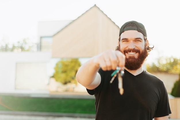 Wesoły młody brodaty mężczyzna trzyma kilka kluczy i wskazuje na nie w pobliżu swojego domu