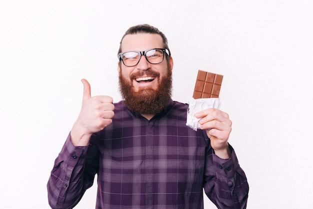 Wesoły młody brodaty mężczyzna w dorywczo noszących okulary i pokazując kciuk do góry i czekoladę