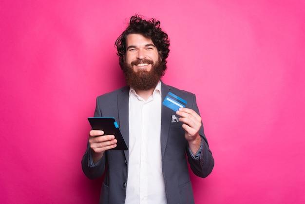 Wesoły młody brodaty mężczyzna w garniturze dokonywania bankowości internetowej za pomocą karty kredytowej i tabletu