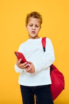 Wesoły młody chłopak rozmawia przez telefon z koncepcją uczenia się studio plecaka szkolnego