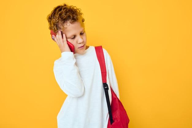 Wesoły młody chłopak rozmawia przez telefon z szkolnym plecakiem na białym tle