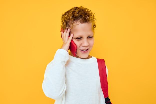 Wesoły młody chłopak w białej bluzie telefon komórkowy czerwony plecak na białym tle