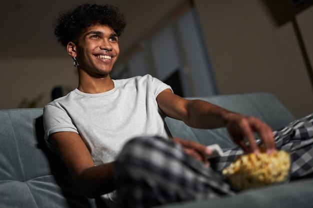 Wesoły młody chłopak w piżamie, biorący popcorn z miski podczas oglądania komedii siedzącej na stole