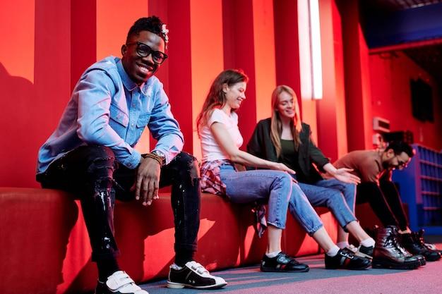 Wesoły młody człowiek afrykański w casualwear i butach do kręgli, patrząc na ciebie, siedząc na tle swoich szczęśliwych przyjaciół