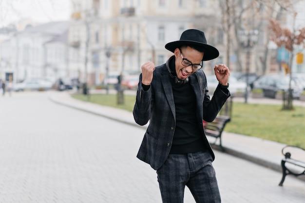 Wesoły młody człowiek afryki szczęśliwy pozowanie w parku w godzinach porannych. zewnątrz portret szczupły stylowy facet w kraciastym garniturze wyrażający pozytywne emocje.