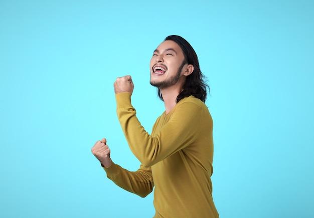 Wesoły młody człowiek azji, podnosząc pięści z uśmiechem na twarzy, zachwycony, tak gest, świętuje sukces na niebieskim tle.