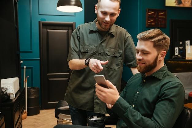 Wesoły młody człowiek coraz strzyżenie przez fryzjera siedząc w fotelu.