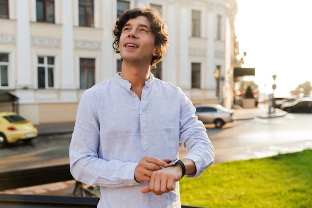 Wesoły młody człowiek dorywczo dostosowując swój inteligentny zegarek