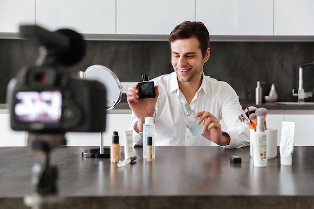Wesoły młody człowiek filmujący swój odcinek blogu wideo