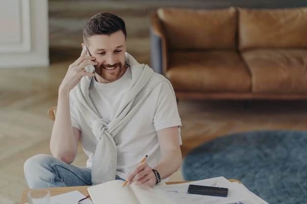 Wesoły młody człowiek freelancer lub męski przedsiębiorca rozmawia z klientem na telefonie komórkowym i robi notatki w notebooku podczas pracy zdalnej z domu, siedząc w salonie ze skórzaną sofą