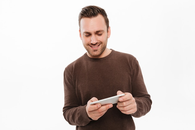 Wesoły młody człowiek grać w gry przez telefon komórkowy