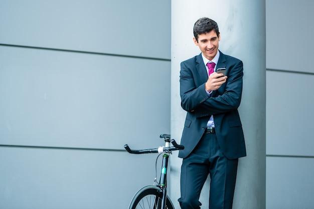 Wesoły młody człowiek komunikuje się przez telefon komórkowy, czekając na zewnątrz w pobliżu nowoczesnego budynku biznesowego