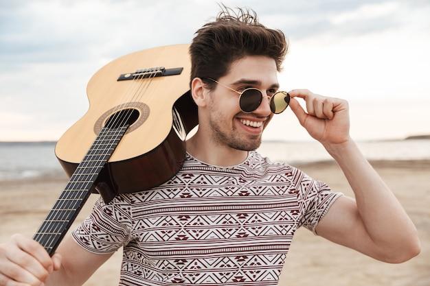 Wesoły młody człowiek niosący gitarę, stojący na plaży