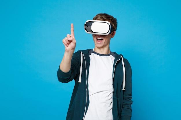 Wesoły młody człowiek patrząc na zestaw słuchawkowy, dotykając czegoś w rodzaju naciśnij przycisk, wskazując na pływający wirtualny ekran na białym tle na niebieskiej ścianie. koncepcja życia emocje ludzi.