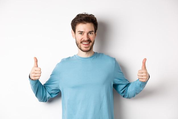 Wesoły młody człowiek pokazujący kciuki do góry i uśmiechnięty, polecający dobry produkt, chwaląc wybór, stojąc na białym tle