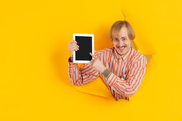 Wesoły młody człowiek pozuje w podartej żółtej ścianie z papieru, emocjonalny i wyrazisty
