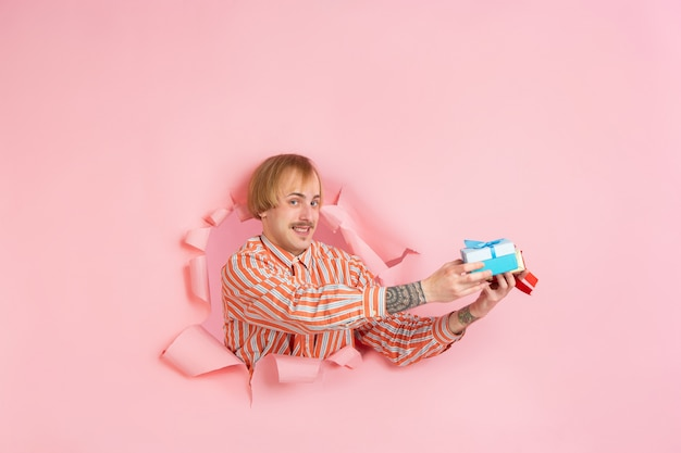 Wesoły młody człowiek pozuje w rozdartej ścianie z papieru koralowego, emocjonalny i wyrazisty