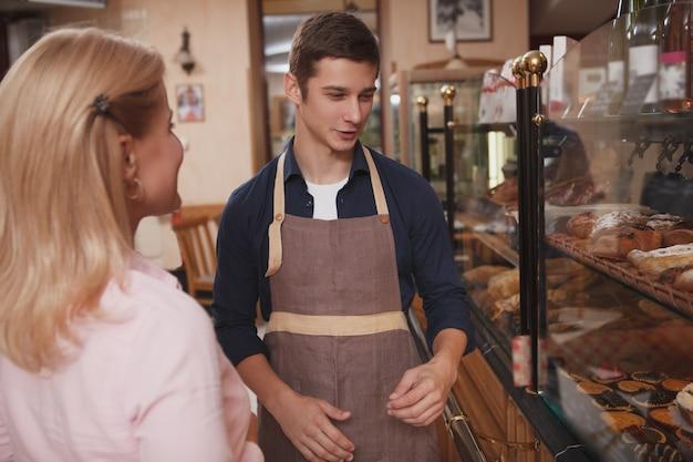 Wesoły młody człowiek pracujący w piekarni, pomagając swojemu klientowi