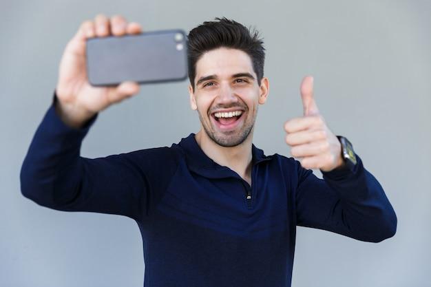 Wesoły młody człowiek przy selfie na białym tle nad szary, kciuki do góry