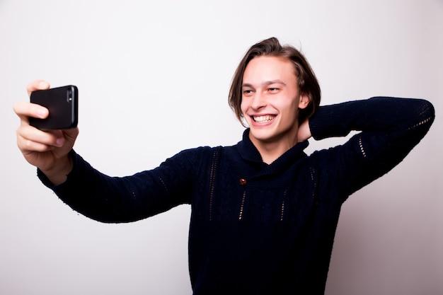 Wesoły młody człowiek robi selfie z czarnym smartfonem