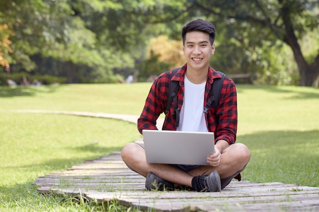 Wesoły młody człowiek siedzi w parku i korzysta z laptopa