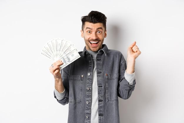 Wesoły młody człowiek skacze z podniecenia i pokazuje dolary, wygrywa nagrodę pieniężną, zarabia pieniądze i raduje się, stojąc na białym tle.