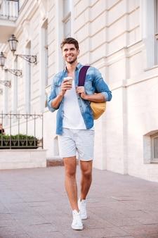 Wesoły młody człowiek spacerujący z plecakiem i pijący kawę w mieście