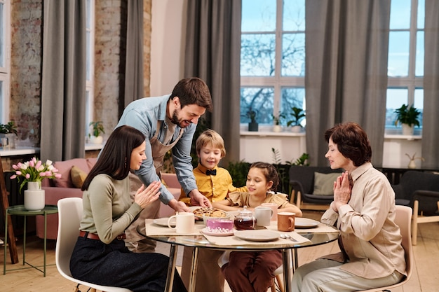 Wesoły młody człowiek stawia talerz z ciastkami na podanym stole z ciastem i herbatą, jednocześnie opiekując się rodziną z dwójką dzieci, żoną i matką