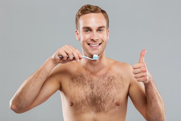 Wesoły młody człowiek trzyma szczoteczkę do zębów i pokazuje kciuk w górę
