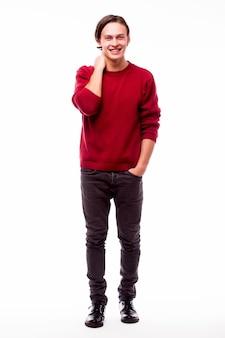 Wesoły młody człowiek, trzymając się za ręce w kieszeniach i patrząc na przód, stojąc przed białą ścianą