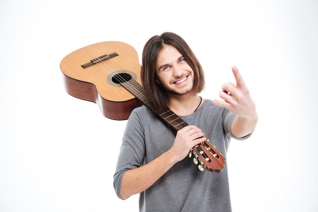Wesoły młody człowiek trzymający gitarę na ramieniu i wykonujący rockowy gest na białym tle