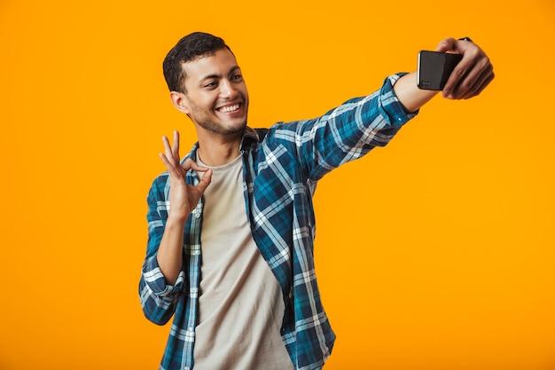 Wesoły młody człowiek ubrany w kraciastą koszulę stojący na białym tle nad pomarańczową ścianą, biorąc selfie