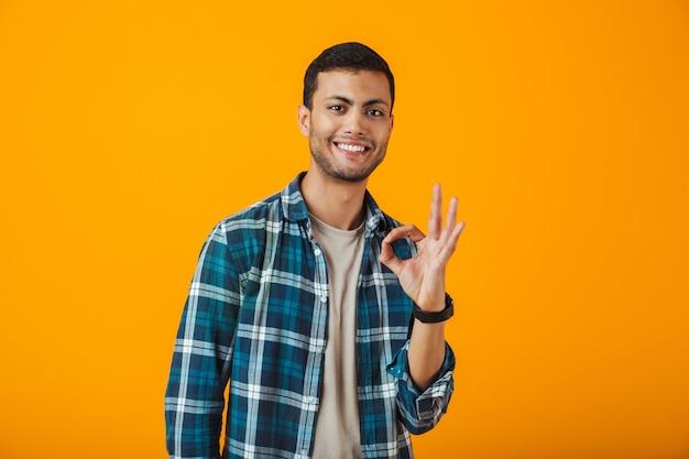Wesoły młody człowiek ubrany w kraciastą koszulę stojący na białym tle nad pomarańczową ścianą, pokazując ok