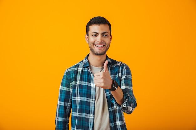 Wesoły młody człowiek ubrany w kratę koszulę stojący na białym tle nad pomarańczową ścianą, dając kciuki do góry