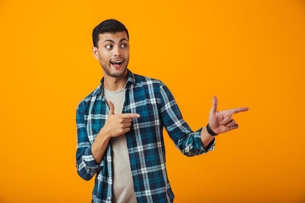 Wesoły młody człowiek ubrany w kratę koszulę stojący na białym tle nad pomarańczową ścianą, wskazując palcem na miejsce