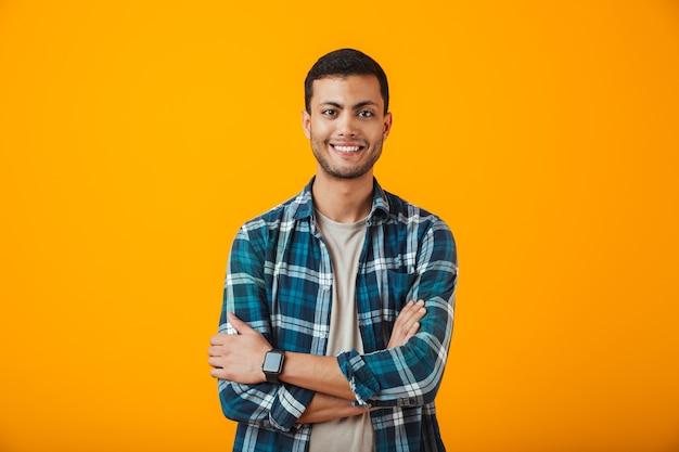Wesoły młody człowiek ubrany w kratę koszulę stojący na białym tle nad pomarańczową ścianą, z założonymi rękami