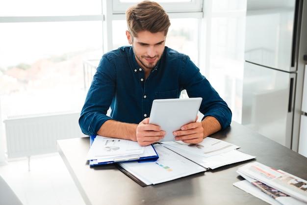 Wesoły młody człowiek ubrany w niebieską koszulę w domu analizując swoje finanse i trzymając tablet w rękach