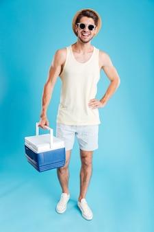 Wesoły młody człowiek w kapeluszu i okularach przeciwsłonecznych stojący i trzymający torbę chłodzącą