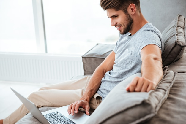 Wesoły młody człowiek w koszulce siedzi na kanapie w domu. praca na komputerze przenośnym i uśmiechnięta.